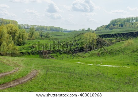 Countryside fields with hills and cloudy sky at summertime in Russia. Summer countryside village. Countryside landscape in Russia. Green grass village. Grass fields, Russia. Green nature of Russia