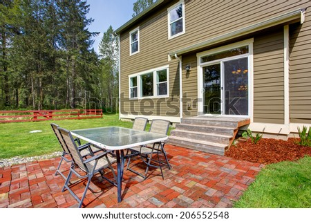 Countryside house exterior with large green backyard and red fence. View of brick floor deck with patio table set - stock photo