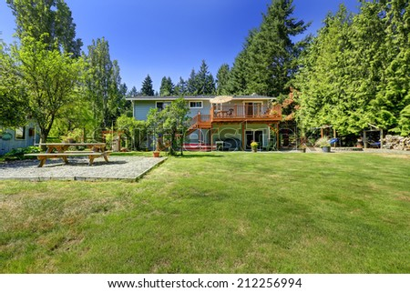 Countryside house with large backyard. View of patio area - stock photo