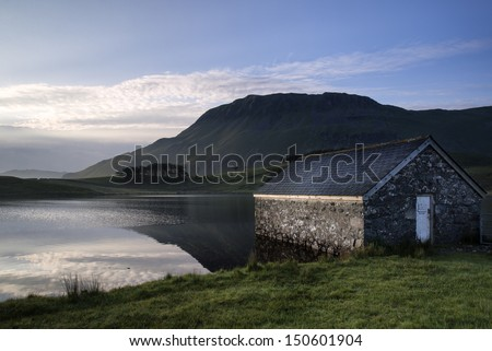 Countryside landscape and mountains in beautiful morning light reflected in calm Cregennen Lakes in Snwodonia National Park - stock photo