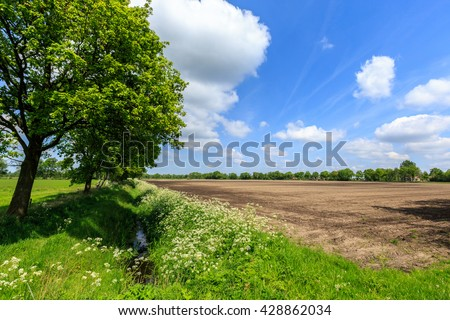 Countryside landscape with ditch and cultivated farm field in spring - stock photo