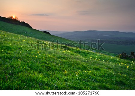 Countryside landscape with sun setting over green hills - stock photo