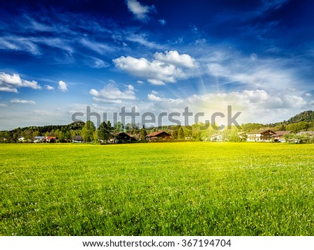 Countryside meadow field with sun and blue sky, Germany - stock photo