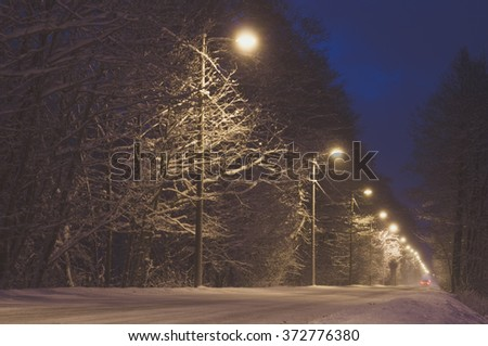 Countryside road covered with snow by night - stock photo