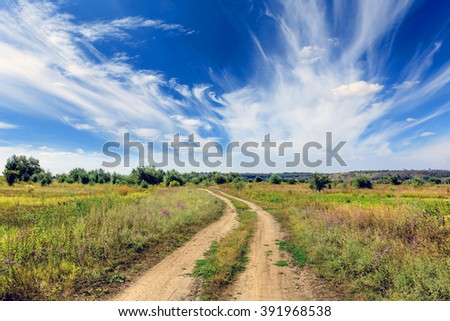 countryside road in steppe under nice clouds un sky - stock photo