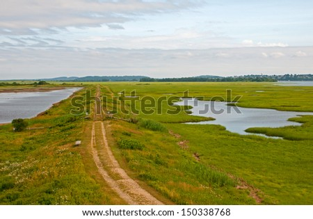 Countryside road through fields and lakes - stock photo
