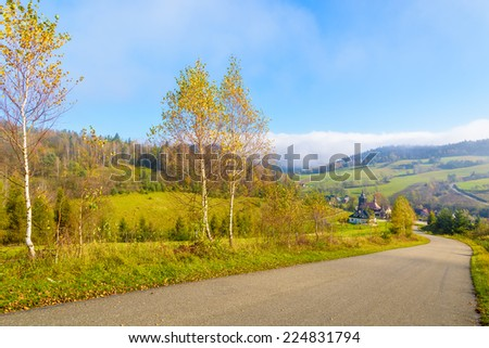Countryside road to village in autumn landscape of Beskid Niski Mountains on sunny day, Poland - stock photo