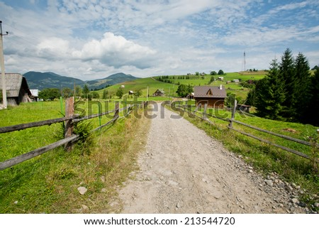 Countryside with village houses and sandy roads nearby forests under clear blue sky - stock photo