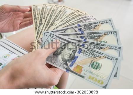 counts money in hands - stock photo