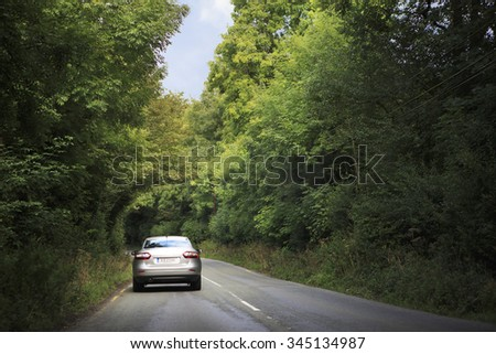 County Kerry, Ireland - August 22, 2014: Car goes on the road in tunnel of trees.