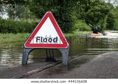 county road in essex of flooded road with a person paddling  down the road in a kayak - stock photo