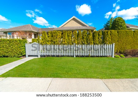 County style long wooden fence with nicely trimmed and landscaped front yard.  Landscape trimming design. - stock photo