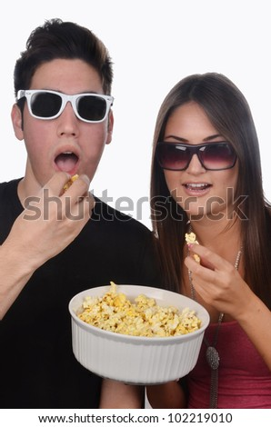 Coupe eating popcorn/Eating Popcorn/Young couple eating popcorn - stock photo