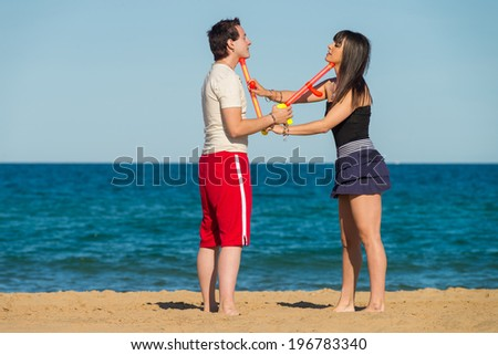 Couple about to set up a water gun fight on the beach - stock photo