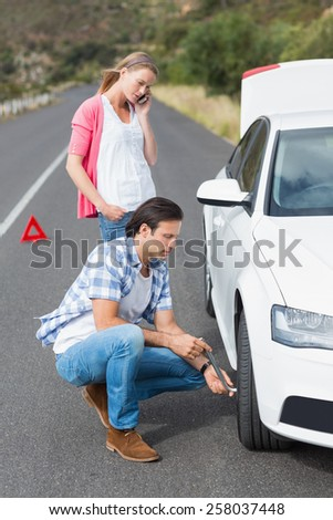 Couple after a car breakdown at the side of the road - stock photo