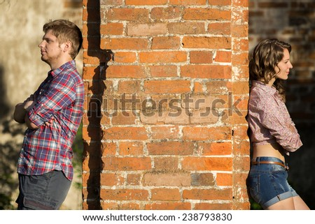 Couple after an argument stands on different sides of the wall - stock photo