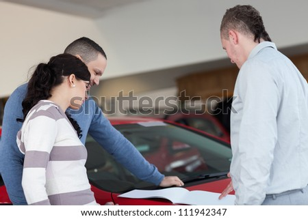 Couple and a salesman looking at a document in a car shop