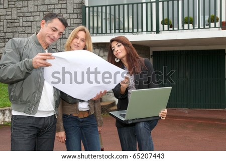 Couple and architect looking at plan of a house - stock photo