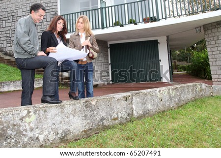 Couple and architect looking at plan of a house