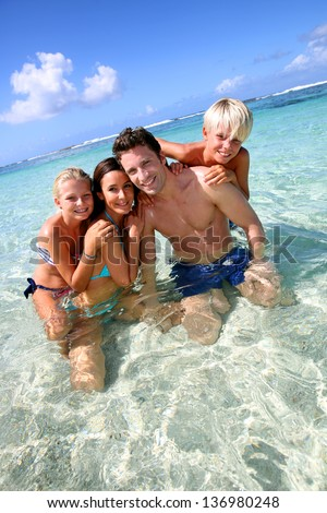 Couple and children in crystal clear water - stock photo