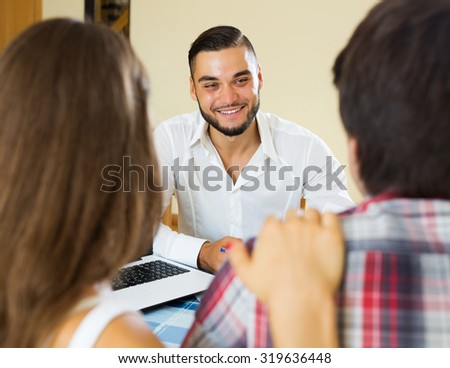 Couple and happy salesman talking cheerfully about purchase at home