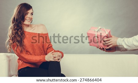 Couple and holiday concept. man holding present in hands surprising cheerful woman with gift box - stock photo