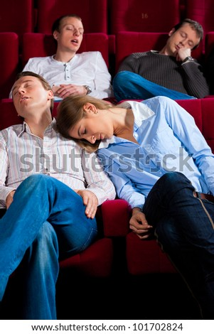 Couple and other people, probably friends, in cinema watching a movie, it seems to be a boring movie - stock photo