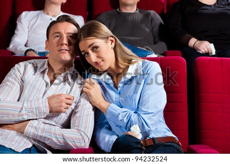 Couple and other people, probably friends, in cinema watching a movie; it seems to be a romantic movie - stock photo