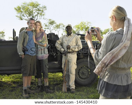 Couple and safari guide posing by jeep while young woman taking photograph - stock photo