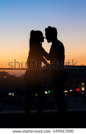 Couple and sunset sky background. Silhouettes of woman and man. Moments worth living for.
