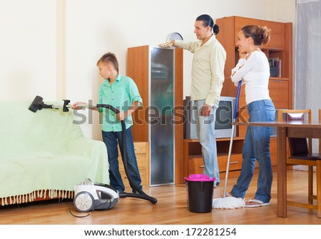 Couple and teenager boy cleaning with vacuum cleaner in living room