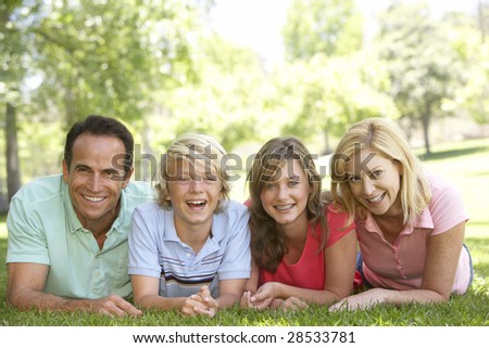 Couple And Their Teenage Children Lying On Grass - stock photo