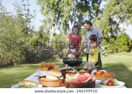 Couple and two children at the garden grill with dining table in foreground - stock photo