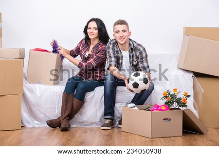 Couple are moving into a new home and unpacking boxes. - stock photo