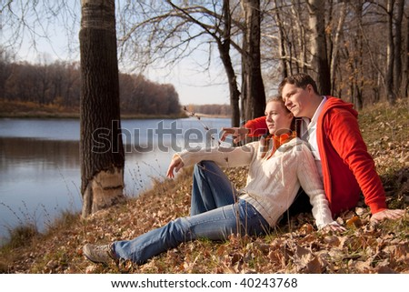 couple are siting on grass and looking forward