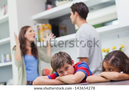 Couple arguing behind their children in the kitchen - stock photo
