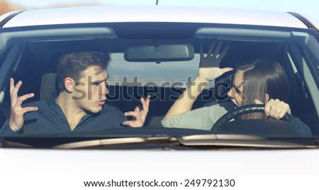 Couple arguing while she is driving a car in a dangerous situation - stock photo