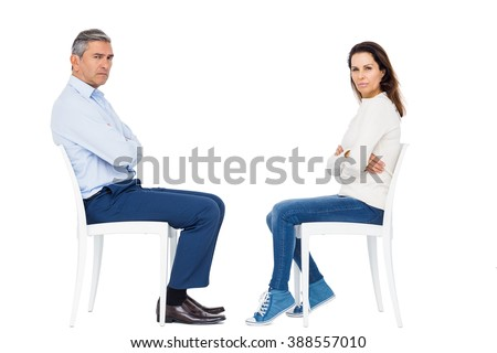Couple arguing while sitting against white background - stock photo