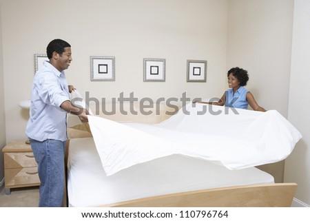 Couple arranging bedsheet on bed - stock photo