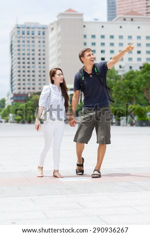 Couple asian girl and caucasian man tourist smile point finger sightseeing, mix race friends outdoor city street