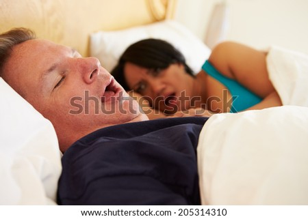 Couple Asleep In Bed With Man Snoring - stock photo