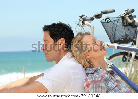 Couple asleep with bikes by the sea - stock photo