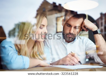 Couple at cafe reading bank contract document - stock photo