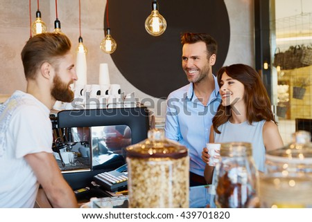 Couple at cafe talking barista, buying coffee - stock photo