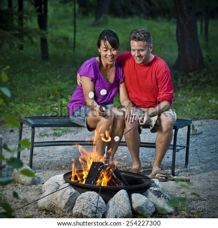 Couple At Campfire - stock photo