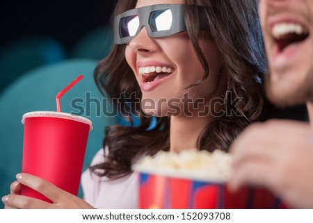 Couple at cinema. Cheerful couple in three-dimensional glasses watching movie at the cinema