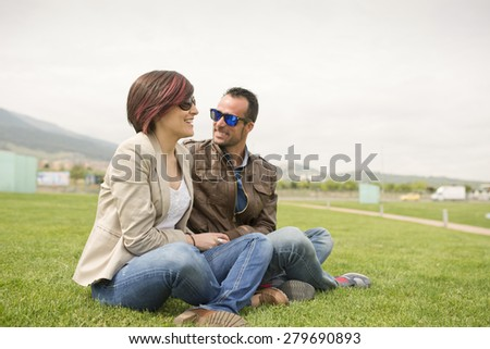 Couple at city park with sunglasses on grass laughing