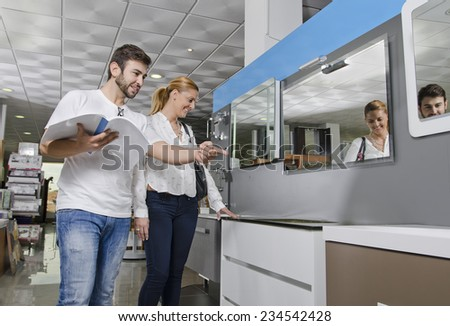 Couple at furniture and bath store looking catalog - stock photo
