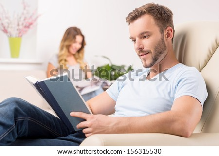 Couple at home. Cheerful young man reading book while his girlfriend sitting on the background and smiling - stock photo