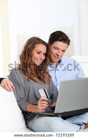 Couple at home doing online shopping - stock photo